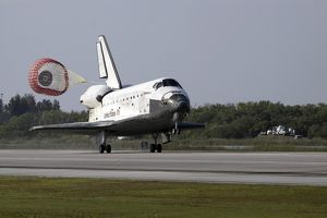 With drag chute unfurled, space shuttle Discovery lands on Runway 33 at the Shuttle