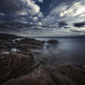 Huge rocks on the shore of a sea against a cloudy sky, Sardinia, Italy