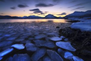 Ice flakes drifting against the sunset in Tjeldsundet strait, Troms County, Norway