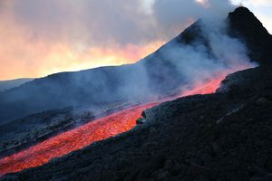 Lava flowing from base of hornito during eruption of Mount Etna volcano, Sicily, Italy