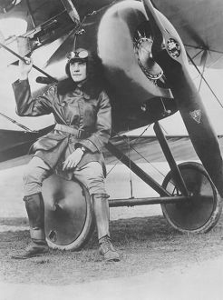 Lieutenant Earl Carroll seated on the wheel of his fast scout airplane