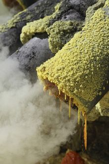 Molten sulphur trickling out of condensation pipe, Kawah Ijen volcano, Java, Indonesia