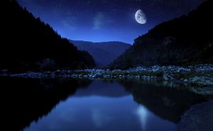 Moon rising over tranquil lake and forest against starry sky, Bulgaria