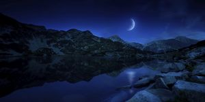Moon rising over tranquil lake and mountains in Pirin National Park, Bulgaria