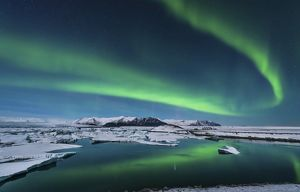 The northern lights dance over the glacier lagoon in Iceland