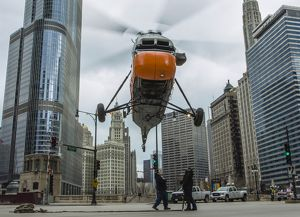 An S-58T helicopter comes down to street level in Chicago, Illinois