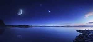 Tranquil lake against starry sky, moon and falling meteorite, Finland