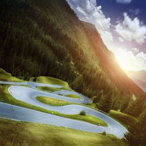 Winding road in a forest of Dolomite Alps at sunset, Northern Italy