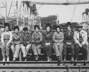 Women welders wearing protective clothing and seated outdoors